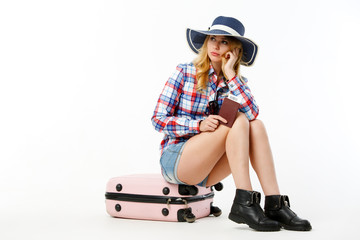 Image of blonde in hat with passport sitting on suitcase