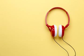 Photo of red with white headphones for music on clean yellow background