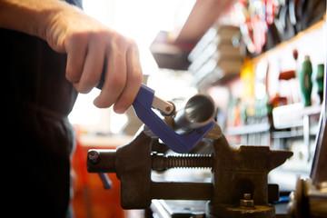 Photo of master mending pipe in workshop