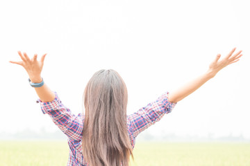Young girl spreading hands with joy and inspiration facing the sun,sun greeting,freedom ,freedom concept
