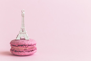 Macaron biscuit and Eiffel Tower on pastel pink background.