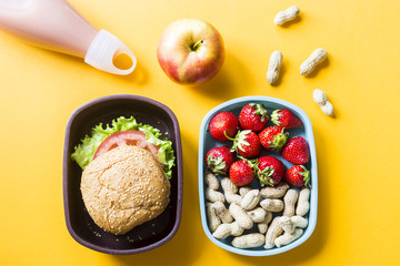Photo sur Plexiglas Assortiment Lunch for a child who is in school with them. Sandwich, strawberries and peanuts in plastic boxes. Next to the apple and a bottle of juice. Top view, flat lay