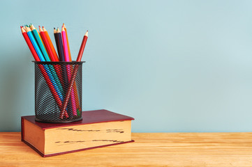 book and colorful pencils on wooden table