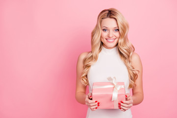 Portrait with copy space, empty place of pretty, charming, cute, lovely, sweet, cheerful girlfriend having packed gift box in hands looking at camera isolated on pink background.Advertisement concept