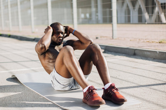African American man works out his abs lying on the ground outside