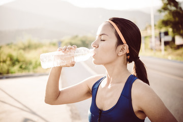 Sporty woman drinking water outdoor on sunny day