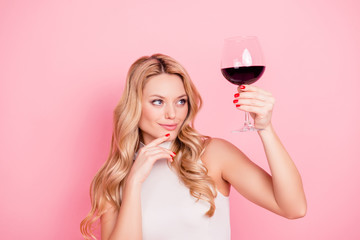 Portrait of ponder minded,  expert, elegant pretty girlfriend looking at raised glass with alcohol beveragein hand with evaluative view isolated on pink background
