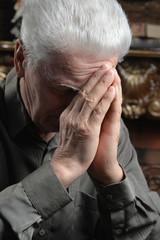 Portrait of Sad senior man praying