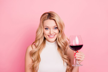 Portrait of foolish cheerful girlfriend having glass with dry semi-sweet red wine in hand looking at camera isolated on pink background