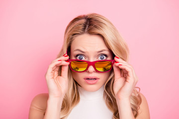 Portrait of frustrated sad unhappy girlfriend with negative upset reaction looking out glasses on her face at camera holding eyelets with two hands isolated on pink background