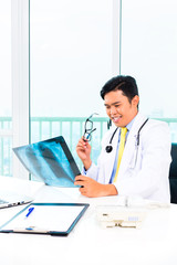 Asian doctor diagnosis X-ray photograph in his medical office wearing stethoscope