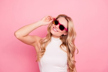 Portrait of lovely positive stylish girlfriend with beaming smile, fashionable successful confident chick in summer glasses holding eyelet with hand isolated on pink background