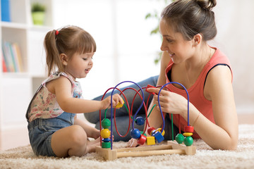 Kid girl plays with educational toy in nursery at home. Happy mother looking at her smart child daughter.