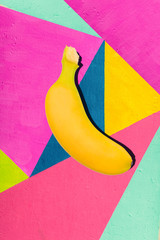 Bright yellow banana on geometric background of wall with bright tones