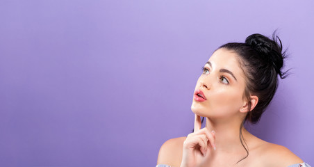 Young woman looking upward on a solid background