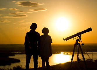 Silhouettes of couple - boy and girl near telescope on the hill at summer sunset