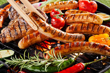 Summer barbecue with sizzling sausages over a fire