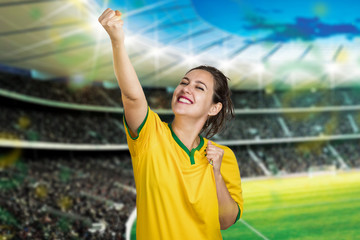 Girl in the stadium cheering for Brazil with hope that the Brazilian team will win the world cup along with the other fans. Crowded world cup stadium and fan celebrating soccer