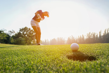 Poster Golf Golfer asian woman focus putting golf ball on the green golf on sun set evening time.. Healthy and Lifestyle Concept