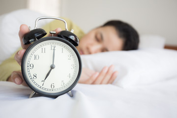 Asian woman's hands are closing the alarm clock at the bedroom.