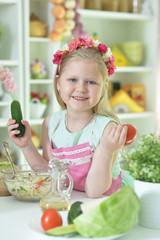 Cute little girl making dinner