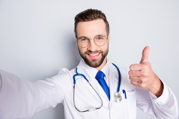 Self portrait of positive trendy doc in white outfit with tie and bristle having stethoscope on his neck shooting selfie showing thumb up, like sign with finger, hand over grey background