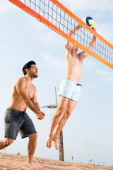 Two friends are playing in volleyball