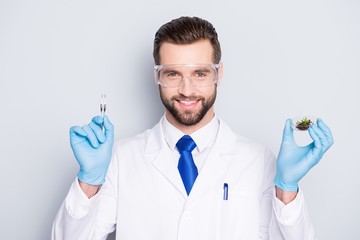 Portrait of attractive biologist in white outfit with tie, showing having forceps and vial with field and small plant, going to make expertising, inspection, isolated on grey background