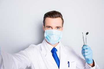 Self portrait of successful cheerful dentist in white lab coat, blue tie, shooting selfie on front camera, holding tools, having leisure, fun, video call, isolated on grey background