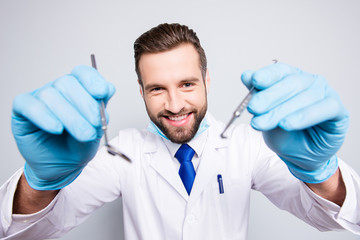 Portrait of positive comic dentist with stubble in white lab coat, blue tie in working process on grey background, treat, examine cavity, searching for sick tooth, holding tools in hands