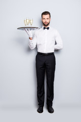 Full size fullbody portrait of concentrated man in classic white shirt and black bowtie holding hand behind the back and tray with three glasses of sparkling wine, isolated on grey background