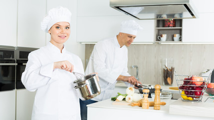 Man cook and woman standing with whisk, professional chefs in uniform