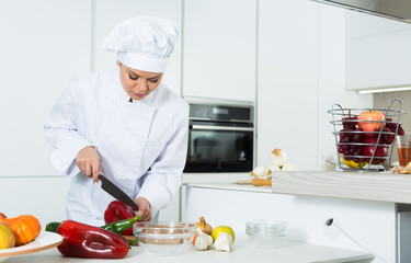 Young woman cook preparing vegetables in white uniform