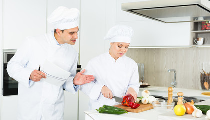 Female and male young cooks with paper recipe in uniform working