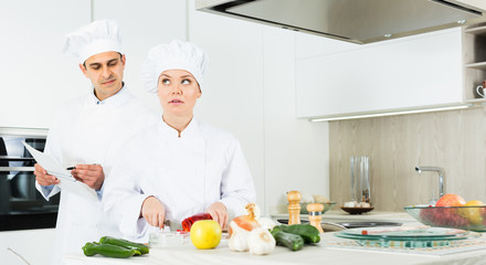 Man and woman kitcheners in uniform are cutting vegetables for salad in the kitchen