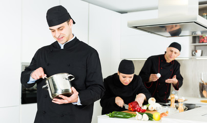 Man chef preparing food with whisk, team working on kitchen