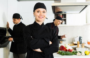 Professional woman chef  in black uniform standing on kitchen