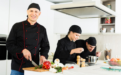 Team of  woman and man chefs in black uniform preparing food