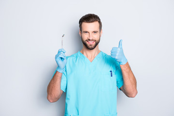 Portrait of joyful cheerful dental assistant in lab blue uniform gesturing thumbup approve advice yes done sign with finger, having tool in hand, isolated on grey background
