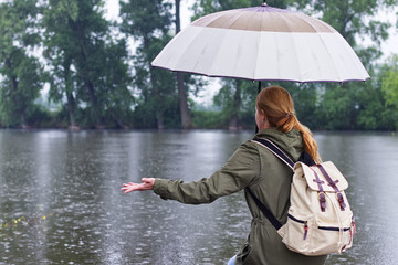 Woman with umbrella and backpack standing in rain on the riverside