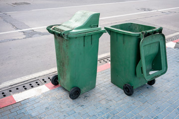 Two green public dirty trash can on street