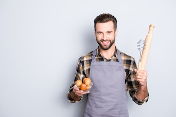Portrait with copyspace, empty place for advertisement of attractive cheerful cook is ready to make some meal, having showing equipments, standing over grey background