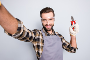 Self portrait of joyful cheerful man with stubble shooting selfie on front camera, showing pliers in arm, having fun, leisure, video-call, isolated on grey background