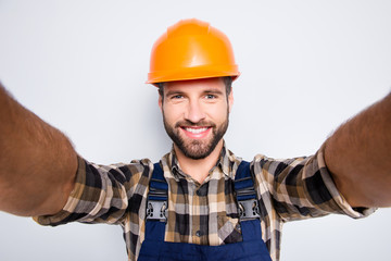 Portrait of handsome cheerful repairer in safety helmet with stubble shooting selfie on smart phone with two hands, wearing shirt and overalls, isolated on grey background