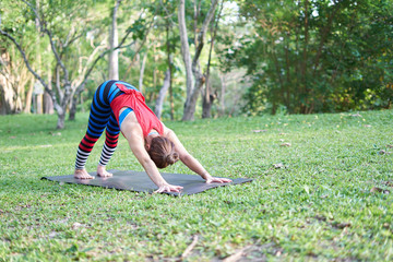 A woman doing yoga exercises at outdoor in a park.