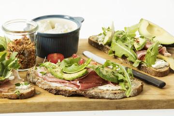 rustikales Zwiebelbrot mit Frischkäse, Parmaschinken, Avocado, Ruccola, Thymian, Chiliraspeln und Tomate, Studio