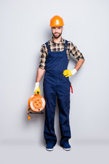 Full size fullbody portrait of cheerful joyful electrician with bristle in overall, shirt, holding equipment with rolled cable in hand and arm on waist, looking at camera, isolated on grey background
