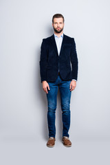 Full size body portrait, snap of attractive trendy teacher with stubble, looking at camera, isolated over grey background, wearing jacket, jeans, shirt