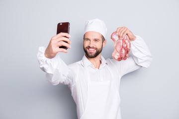 Portrait of attractive handsome butcher with stubble shooting selfie on front camera of smart phone, holding fresh meat in hand, blogger having video-call, isolated on grey background