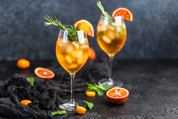 Cocktail with orange juice and ice cubes. Glass of orange soda drink on dark background